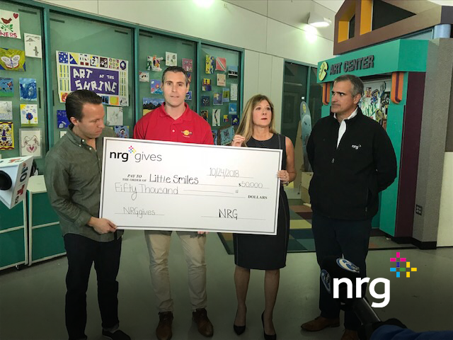 Diane O'Mara, Steve Grandizio and Jeff Haas are presented with a $50,000 check from NRG at Shriners Hospital. Little Smiles PA won the Pick NRG contest
